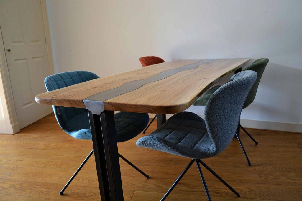 Massief-iepen-tafel-met-stalen-frame-en-inlegwerk.-Stoelen-zijn-een-praktisch-complementair-goed.MeubelMarcker